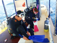 ボートで器材を装着するダイバー