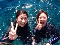 海面に浮かんで笑顔の女性ダイバー2名